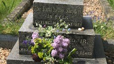 A grave inscribed The Lord is my Shepherd and with flowers