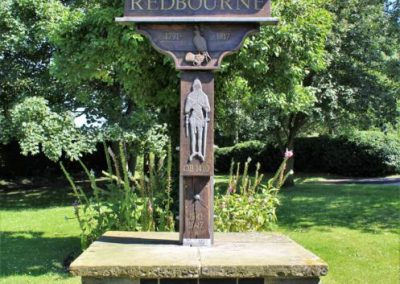 A monument depicting the word Redbourne, a knight and a duck