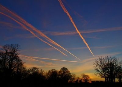 Several aeroplane vapour trails across an evening sky
