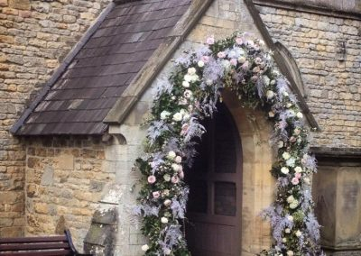 An arch of wedding flowers around the church entrance