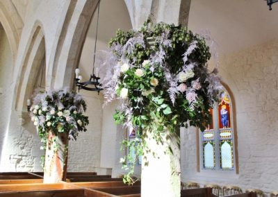 Wedding flowers decorating church pillars