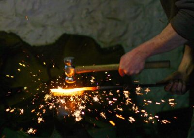 Sparks from a blacksmith hitting some white hot metal with a hammer