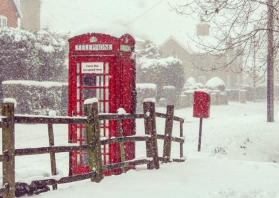 An old-fashioned red telephone box and red post box in a snowstorm