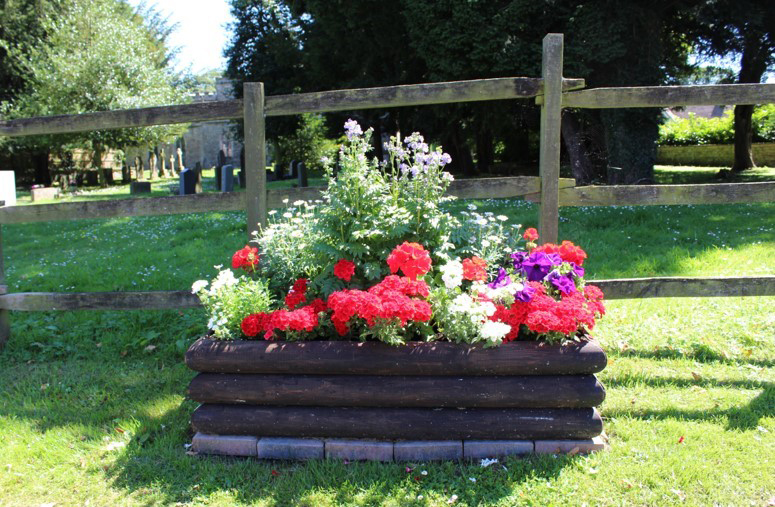 Roadside planter with mixed flowers by a fence