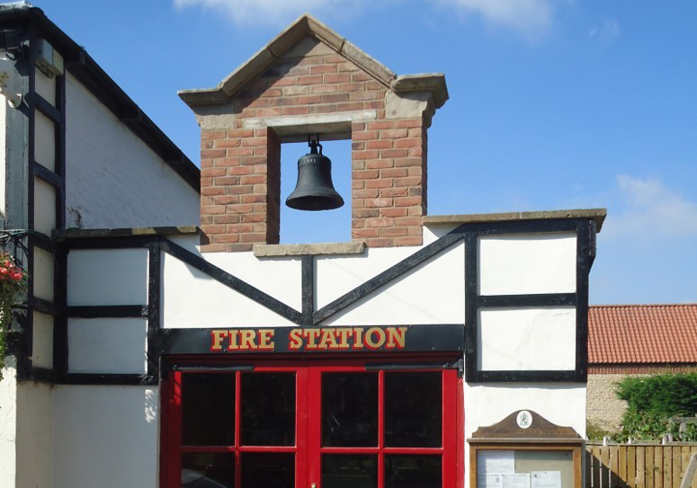 An old fire station door with a bell mounted in a brick arch above it